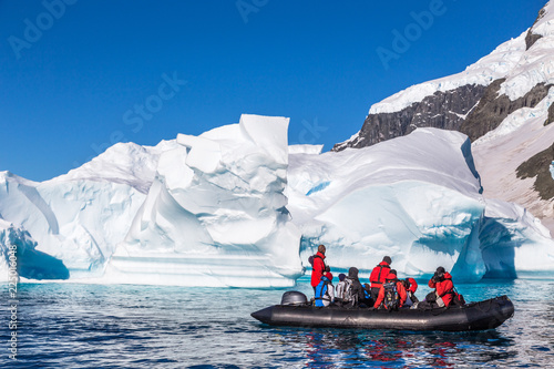 Photo sur Aluminium Antarctique Boat full of tourists explore huge icebergs drifting in the bay