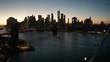 dusk view of NYC flying backward over Manhattan Bridge