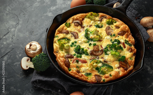 Homemade Frittata with mushrooms, broccoli, feta cheese, green peas and bacon on cast iron skillet