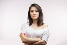 Close Up Studio Shot Of Calm Asian Young Woman With Healthy Clean Skin, Gorgeous Dark Hair And Expressive Big Eyes In White T-shirt Looking At Camera With Calm And Serious Expression.