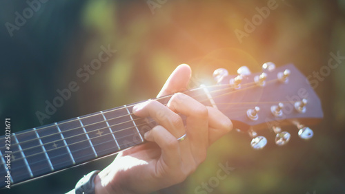 Carta da parati  The man is playing guitar in the garden, Close-up male hand playing on acoustic guitar outdoor with bokeh and rays of sunlight