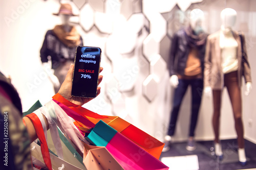 Fotobehang Art Studio People, sale, consumerism, advertisement concept - close up of woman's hand holding shopping bags and smartphone with black friday sale inscription