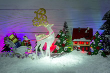 Christmas Composition. Santa Claus In A Sleigh With Gifts, A Fairy-tale White Deer, A Toy Small House With Decorative Lighting A Midst Snow-covered Firs.