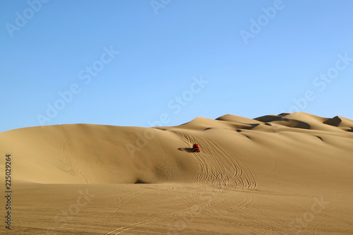 Foto  A red dune buggy running on the immense sand dune of Huacachina, Ica region, Per