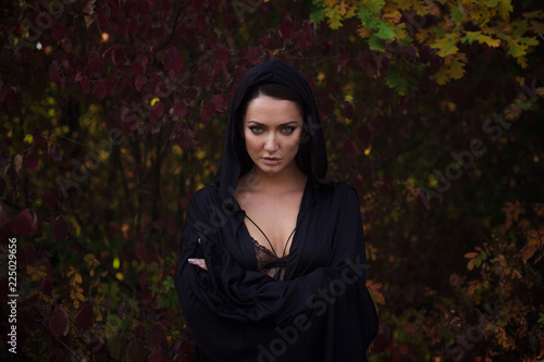 Fotomural Young woman in the black cloak in the autumn forest