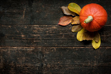Autumn Harvest And Holiday Still Life. Happy Thanksgiving Background. Pumpkin And Fallen Leaves On Dark Wooden Background. Autumn Vegetables And Seasonal Decorations.