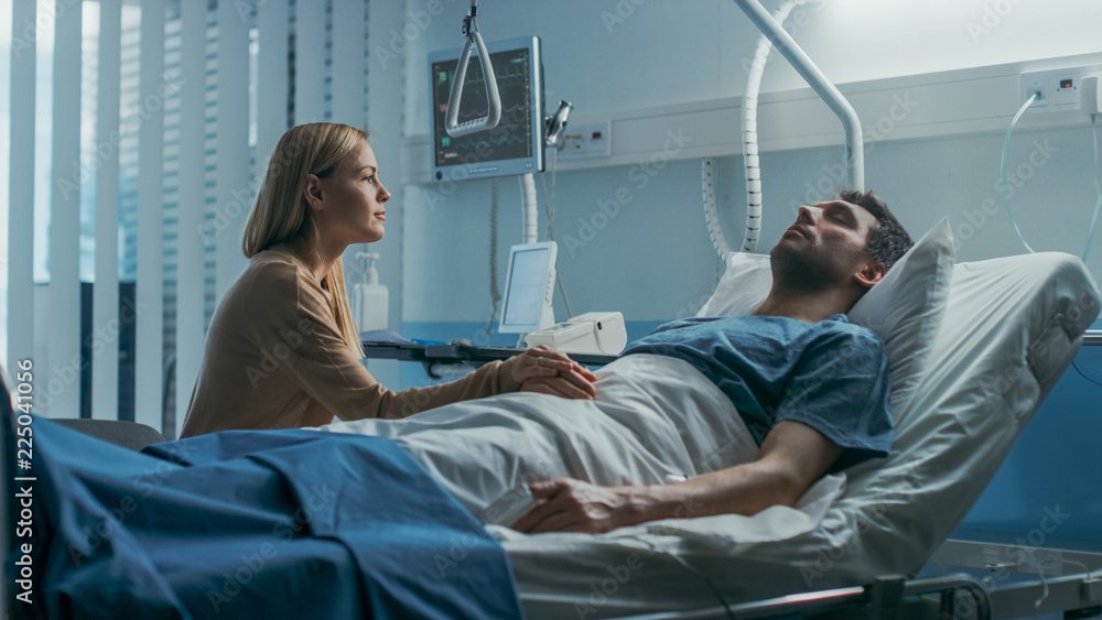 Fototapeta In the Hospital, Worrying Wife Sits Beside the Bed where Her Sick Husband Lies. She Holds His Hand, Talks to Him and Hopes for Recovery.