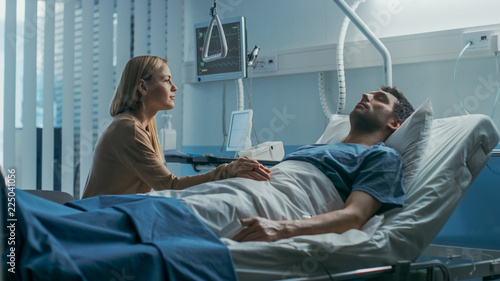 Stampa su Tela  In the Hospital, Worrying Wife Sits Beside the Bed where Her Sick Husband Lies