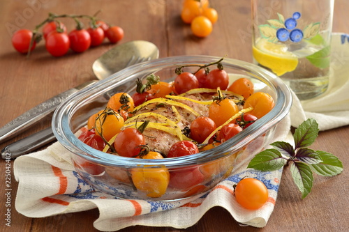 Fotografía  Baked chicken breast with cherry tomatoes in baking dish