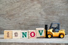 Toy Forklift Hold Block V To Complete Word 19nov On Wood Background (Concept For Calendar Date 19 In Month November)