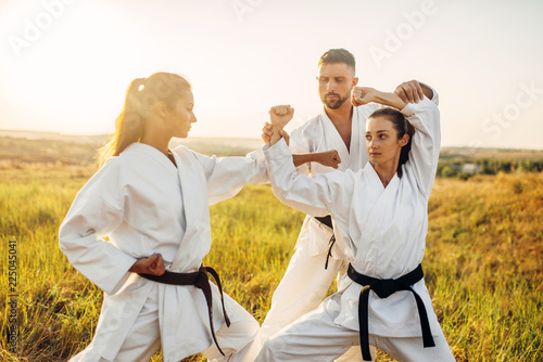 Photo Stands Martial arts Two female fighters on karate training with master