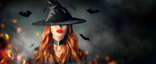 Halloween. Sexy Witch Portrait. Beautiful Young Woman In Witches Hat With Long Curly Red Hair