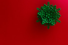 Close-up Of A Green Snowflake Ornament On The Up-right Corner Of A Red Background