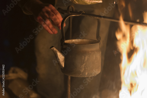 A man is laying dried herb in a kettle boiling on a fire at night Wallpaper Mural