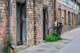 Fototapeta Uliczki - At the old brick building gutters with a lock connected the black bike.