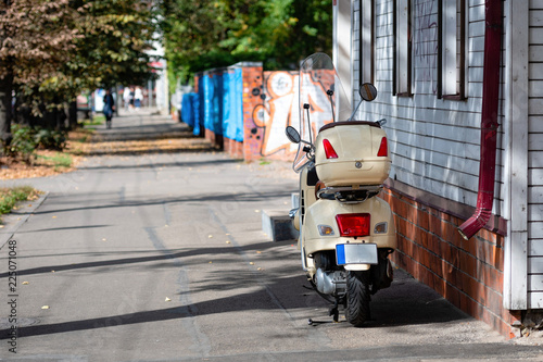 A scooter is packed at the wooden building near the street.