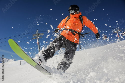 Fotobehang Wintersporten Snowboarder riding down the powder mountain hill on sunny day. Snowboarding in Georgia, Goderdzi