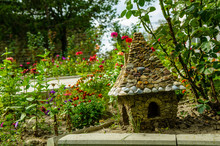 A Small Stone House For Gnomes In A Flower Bed Among The Flowers. Fairytale House