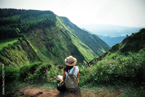 Fotobehang Ontspanning woman traveler holding hat and looking at amazing mountains and forest, wanderlust travel concept, space for text, atmospheric epic moment, azores ,portuhal, ponta delgada, sao miguel