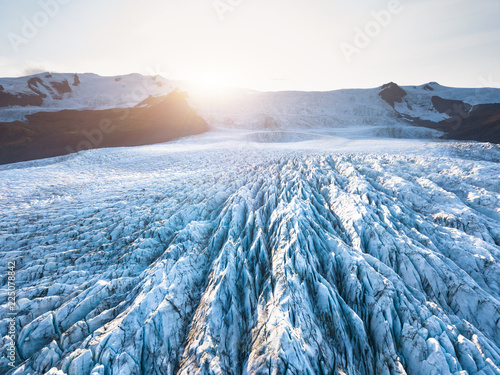 Glacier surface details viewed from above with crevasses and seracs, drone aerial view of Vatnajökull in Iceland, largest icelandic ice cap, beautiful patterns, summer sun