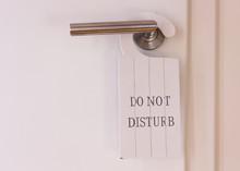 White Do Not Disturb Sign At Restroom Door. Doorhanger Made Of Wood With Print On It.