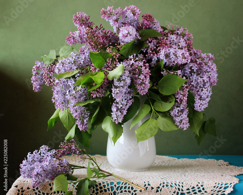 Bouquet of purple lilac in a vase on the table.
