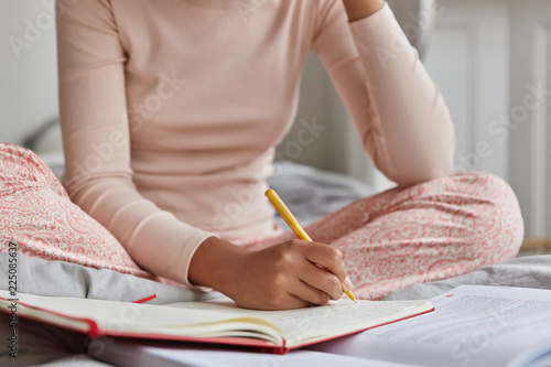 Photo  Unrecognizable woman dressed in casual nightwear, writes in notebook, has inspiration for studying