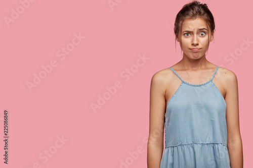 Fotografie, Obraz  Dissatisfied cute teenager has annoyed facial expression, frowns face and purses