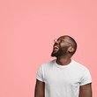 Leinwandbild Motiv Vertical shot of cheerful dark skinned unshaven man looks positively upwards, being in good mood, wears round glasses, white casual t shirt, poses against pink background with free space for your text