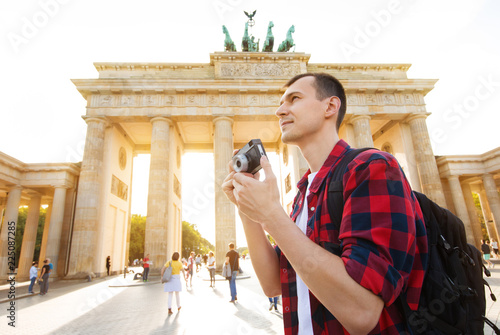 Foto  Travel in Berlin, tourist man with camera in front of Brandenburg Gate, Berlin,