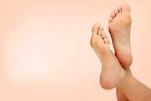 Female Feet Against Pastel Background. Skin Care Concept
