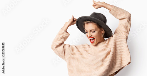 Portrait of beautiful smiling girl in hat and wearing knitted sweater on white background. Woman with bright emotion. Autumn fashion concept. - fototapety na wymiar