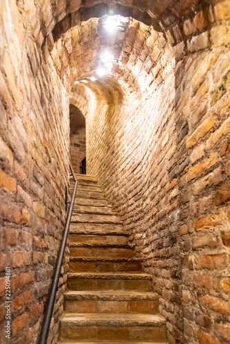 Narrow staircase in old cellar with brick walls.