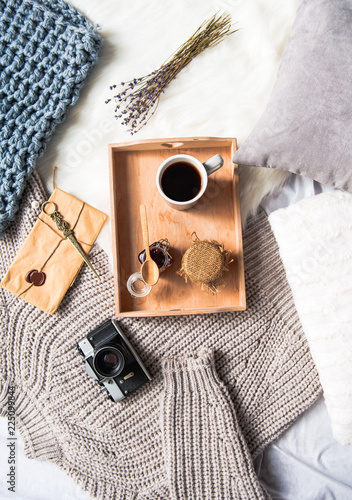 Canvas Prints Autumn Top view cup of coffee and can of honey in tray. Knitted sweater, envelope and bunch of flowers locating on floor. Lunch concept