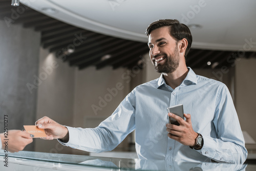 Fotografia Smiling businessman is standing near receptionist in office hall