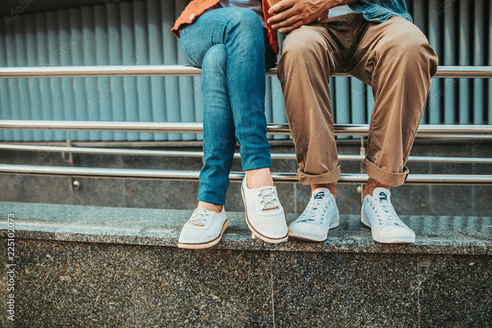 Fototapeta Close up female and man legs wearing modern white shoes. They having leisure on handrail outdoor