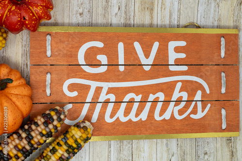Fotografie, Obraz  Give Thanks text phrase Thanksgiving holiday background with plaid pumpkins