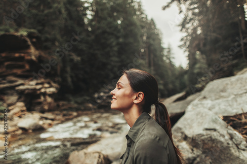 Valokuvatapetti Positive nice young woman smiling while standing in the forest and breathing fre
