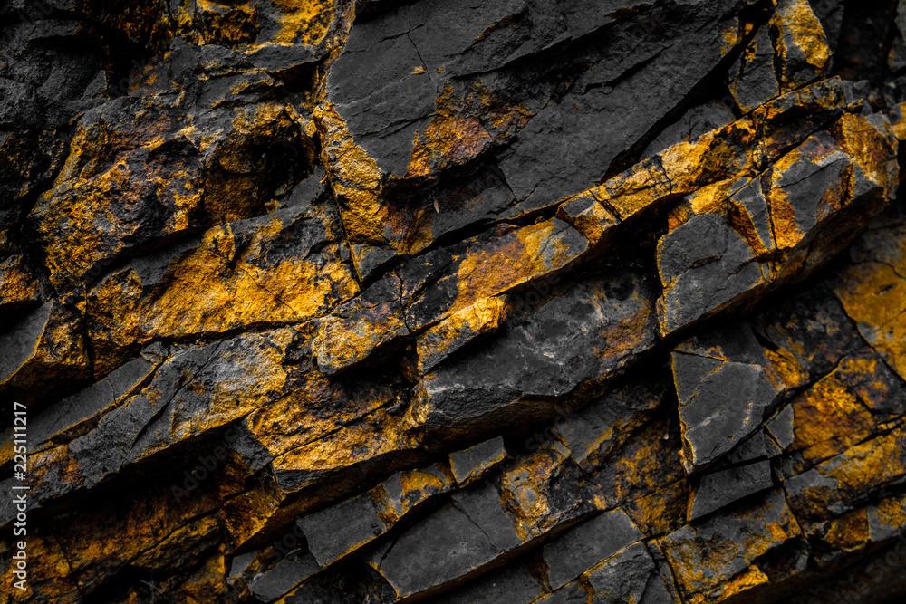Fototapeta black rock background with gold  / yellow colored rocks
