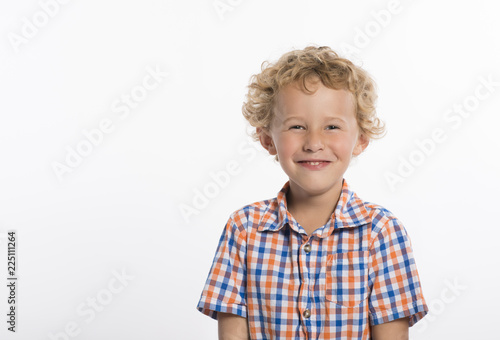 Fotografie, Obraz  Giggling little boy in plaid shirt, isolated on white background