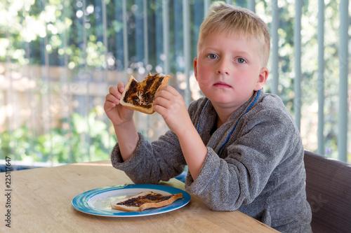 Leinwand Poster Young boy eating vegemite toast for breakfast