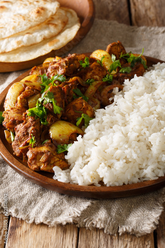 Photo  Traditional recipe for Indian chicken do pyaza (dopiaza) with onion and spice and garnish of rice close-up on a plate with flatbread