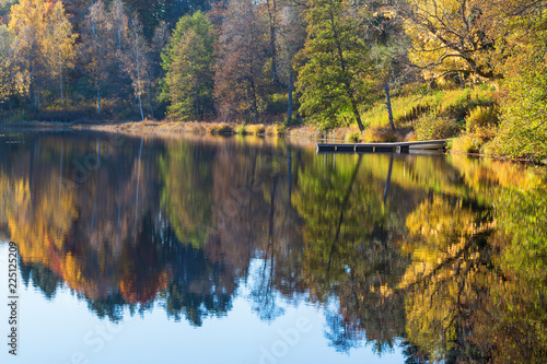 View of a lake with a jetty by the beach and reflections of autumn colors in the water