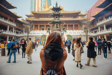Rear View Of Young Woman Traveler Taking Photo Picture At Jing'an Temple In China. Young Asian Woman In Jacket Clothes Using Camera Take A Picture Of Temple In Shanghai.