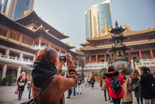 Young Tourist Woman Taking Photo Picture At Jing'an Temple In Downtown Area Of Shanghai, China. Young Asian Woman In Jacket Clothes Using Camera Take A Picture Of Temple In Shanghai.