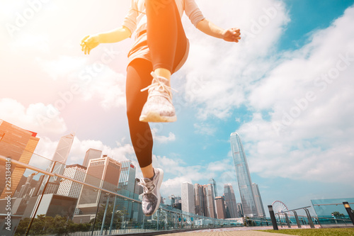 Obraz Woman runner jumping over the camera  with Hong Kong Cityscape in background - fototapety do salonu