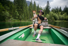 Young Athletic Sporty Man During Weekend City Getaway Rides Vintage Rowing Boat With His Best Friend, Basenji Puppy Dog On His Lap. Smiles And Laughs, Enjoying Nature Outdoor Camping Lifestyle