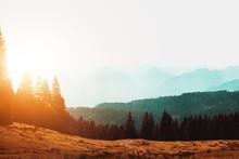 Sun Rising Over A Misty Mountain Landscape