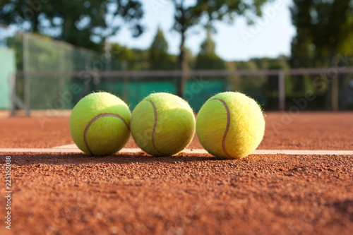 Three tennis balls on court.