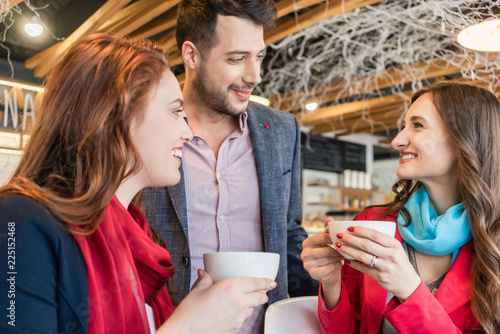Attractive young woman meeting an old friend while sitting and enjoying a hot dr Canvas Print